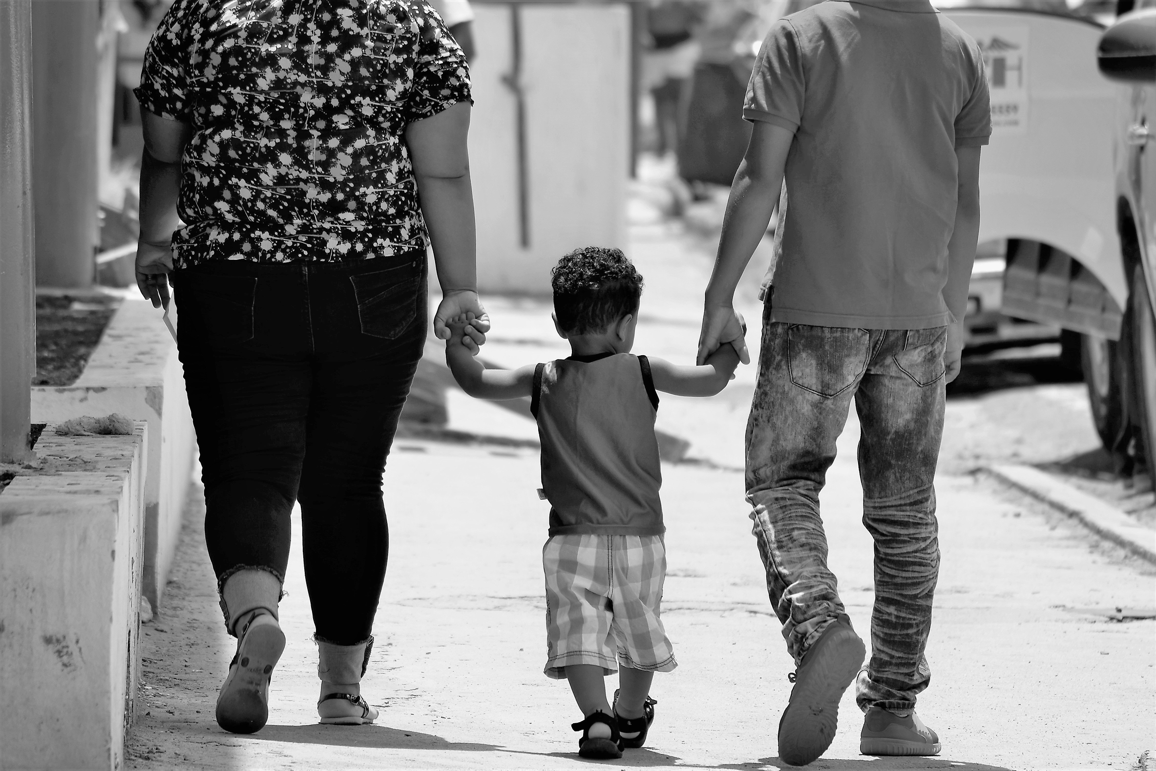 Parents holding hands with toddler walking
